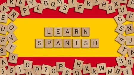 Learn Spanish word written with wooden tiles over Spanish flag. This image can be used for a banner or a print postcard.