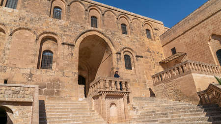 Midyat, Mardin, Turkey - January 2020: Turkish woman visiting Mor Gabriel Deyrulumur Monastry is the oldest surviving Syriac Orthodox monastery in the world.