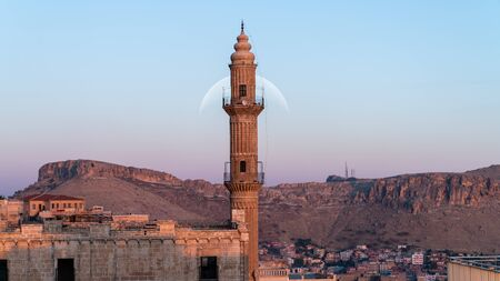 Sehidiye mosque and its minaret with moon rising Mardin old city cityscape