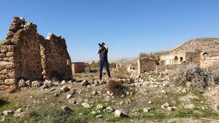 Dereici, Savur, Mardin - January 2020: Tourist taking photos of abandoned Syriac village of Killit Dereici, near Savur town, in the southeastern Turkey