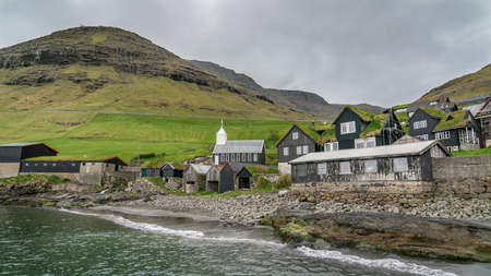 Bour, Faroe Islands - August 2019: Typical nordic village overlooking a fjord surrounded by green mountains . Publikacyjne