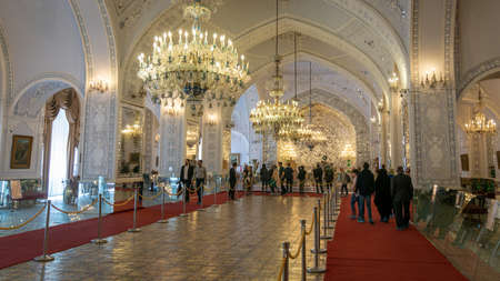 Tehran, Iran - May 2019: Tourists visiting Talar-e Salam or Reception Hall of Golestan palace, decorated with mirror work, relief plaster patterns, mosaic on floor and scenic chandeliers
