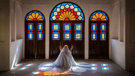 Kashan, Iran - May 2019: Unidentified Iranian woman in chador hijab praying inside Tabatabaei Natanzi Khaneh Historical House