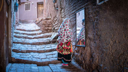 Abyaneh, Iran - May 2019: Unidentified Iranian woman with traditional Abyaneh Persian dress
