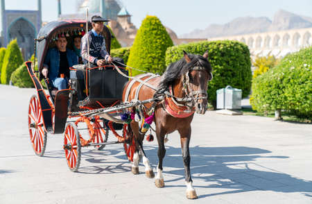 Isfahan, Iran - May 2019: Tourists having a horse carriage ride around Isfahan Naqsh-e Jahan Square also called Imam Square Publikacyjne