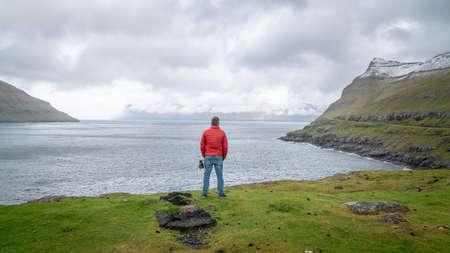Torshavn, Faroe Islands - August 2019: Unidentified man looking at the dramatic landscape in Faroe Islands, Denmark Publikacyjne
