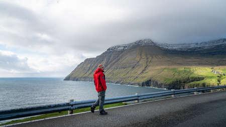 Vidareidi, Faroe Islands - August 2019: Unidentified man looking at the dramatic landscape in Faroe Islands, Denmark