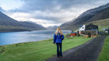 Vidareidi, Faroe Islands - August 2019: Unidentified woman looking at the dramatic landscape in Faroe Islands, Denmark