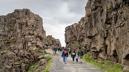 Thingvellir, Iceland - August 2019: Tourists walking along Thingvellir National Park with creek of tectonic plates