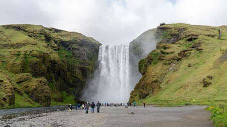 Skogar, Iceland - August 2019: Skogafoss waterfall with tourists visiting in Skogar, south of Iceland. Majestic nature of Iceland.