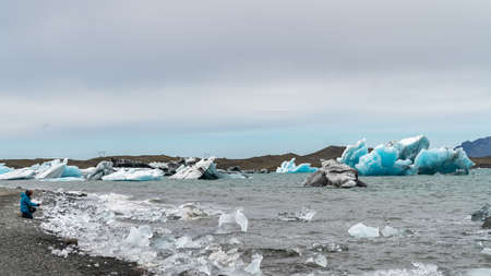 Unidentified woman taking a photo of icebergs in Jokulsarlon glacier lagoon formed with melting ice, Iceland, global warming and climate change concept