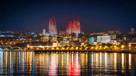 Baku, Azerbaijan - July 2019: Night view of Baku with the Flame Towers skyscrapers, television tower and the seaside of the Caspian sea Publikacyjne