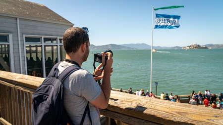 San Francisco, California, USA - August 2019: Man taking photos of Alcatraz Iceland standing in Pier 39 the fisherman's wharf