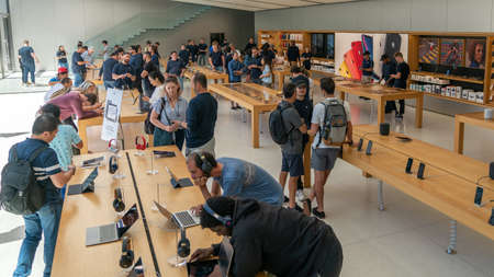 San Francisco, California, USA - August 2019: People examining Apple products laptops phones and tablets at Apple Store in Union Square Publikacyjne