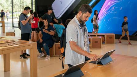 Cupertino, CA, USA - August 2019: Man examining an iPad in Apple Store in Cupertino, Apple Headquarters infinite loop