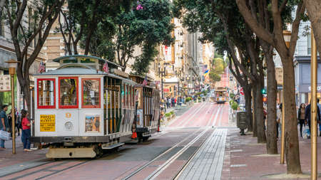 San Francisco, California, USA - August 2019: People riding the cable car in San Francisco. It is the oldest mechanical public transport in California.