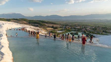 Pamukkale, Turkey - October 2019: Tourists on Pamukkale Travertine pools and terraces. Pamukkale is famous UNESCO world heritage site in Turkey Publikacyjne