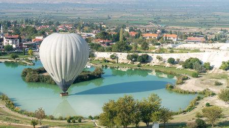 Denizli, Turkey - October 2019: Hot air balloon touching the pool near Pamukkale travertine