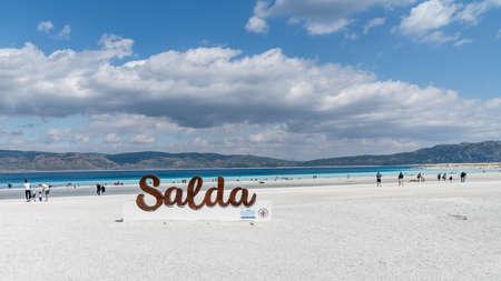 Salda Lake, Burdur, Turkey - October 2019: Salda Lake signage at the beach of Salda lake with tourists. Salda Lake became famous as Maldives of Turkey Publikacyjne