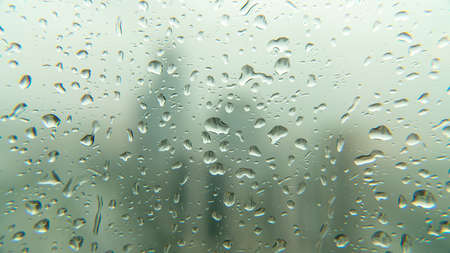 Drops of rain on window glass with blurred skyscraper financial district Istanbul city skyline, Turkey. Autumn Abstract Backdrop
