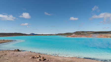 Blue lake in Hverir Myvatn geothermal area with boiling mudpools and steaming fumaroles in Iceland