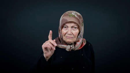 Portrait of a Turkish senior muslim woman with black background. She has a angry expression on her face. Zdjęcie Seryjne