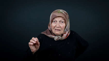 Portrait of a Turkish senior muslim woman with black background. She is surprised, scared and nervous. Zdjęcie Seryjne