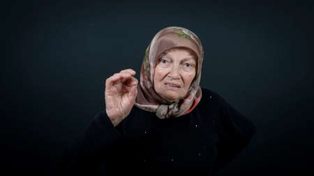 Portrait of a Turkish senior muslim woman with black background. She is scared and nervous.