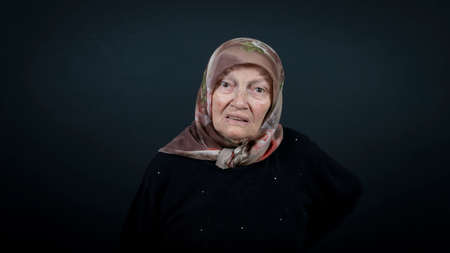 Portrait of a Turkish senior muslim woman with black background. She is nervous, tense and unhappy