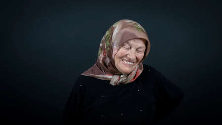Portrait of a Turkish senior muslim woman with black background. She is very happy and laughing. Zdjęcie Seryjne