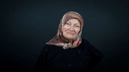 Portrait of a Turkish senior muslim woman with black background. She has a happy smiling expression on her face.