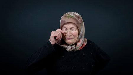 Portrait of a Turkish senior muslim woman with black background. She is sad, unhappy and crying. Zdjęcie Seryjne