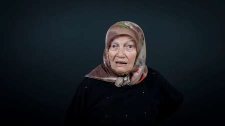 Portrait of a Turkish senior muslim woman with black background. She is surprised, scared and shocked.