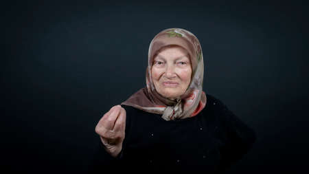 Portrait of a Turkish senior muslim woman with black background. She is showing gourmet sign with fingers tasty delicious and good Zdjęcie Seryjne