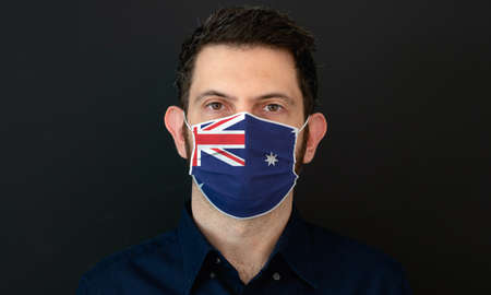 Man wearing Australian flag protective medical face mask. He looks worried and concerned. concept in Australia with black background. Zdjęcie Seryjne