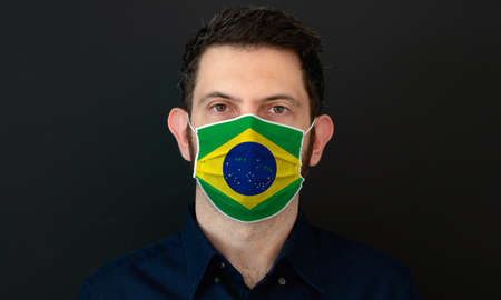 Man wearing Brazilian flag protective medical face mask. He looks worried and concerned. concept in Brazil with black background.