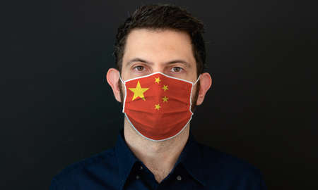 Man wearing Chinese flag protective medical face mask. He looks worried and concerned. concept in China with black background.