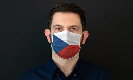 Man wearing Czech flag protective medical face mask. He looks worried and concerned. concept in Czechia with black background.