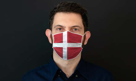 Man wearing Danish flag protective medical face mask. He looks worried and concerned. concept in Denmark with black background.