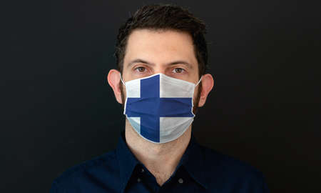 Man wearing Finnish flag protective medical face mask. He looks worried and concerned. concept in Finland with black background. Zdjęcie Seryjne