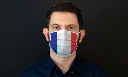 Man wearing French flag protective medical face mask. He looks worried and concerned. concept in France with black background.