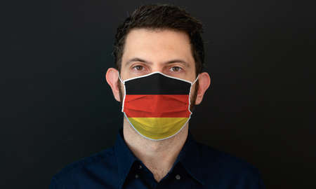 Man wearing German flag protective medical face mask. He looks worried and concerned. concept in Germany with black background.