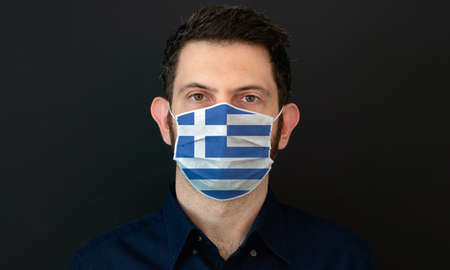 Man wearing Greek flag protective medical face mask. He looks worried and concerned. concept in Greece with black background. Zdjęcie Seryjne