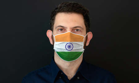 Man wearing Indian flag protective medical face mask. He looks worried and concerned. concept in India with black background.