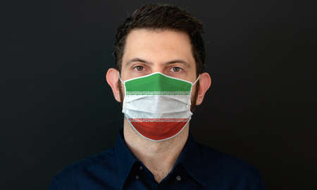 Man wearing Iranian flag protective medical face mask. He looks worried and concerned. concept in Iran with black background.