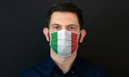 Man wearing Italian flag protective medical face mask. He looks worried and concerned. concept in Italy with black background. Zdjęcie Seryjne