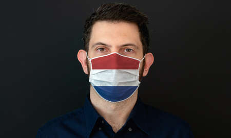 Man wearing Dutch flag protective medical face mask. He looks worried and concerned. concept in Netherlands with black background. Zdjęcie Seryjne