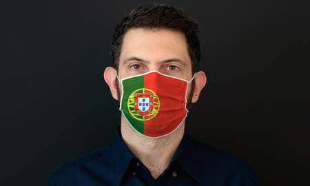 Man wearing Portuguese flag protective medical face mask. He looks worried and concerned. concept in Portugal with black background.