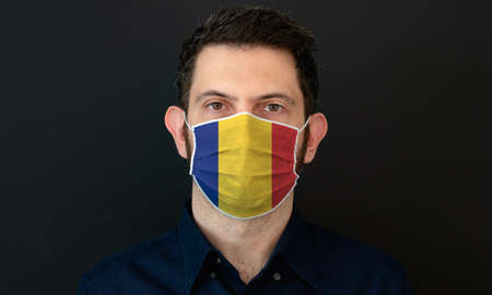 Man wearing Romanian flag protective medical face mask. He looks worried and concerned. concept in Romania with black background.