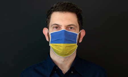Man wearing Ukrainian flag protective medical face mask. He looks worried and concerned. concept in Ukraine with black background.